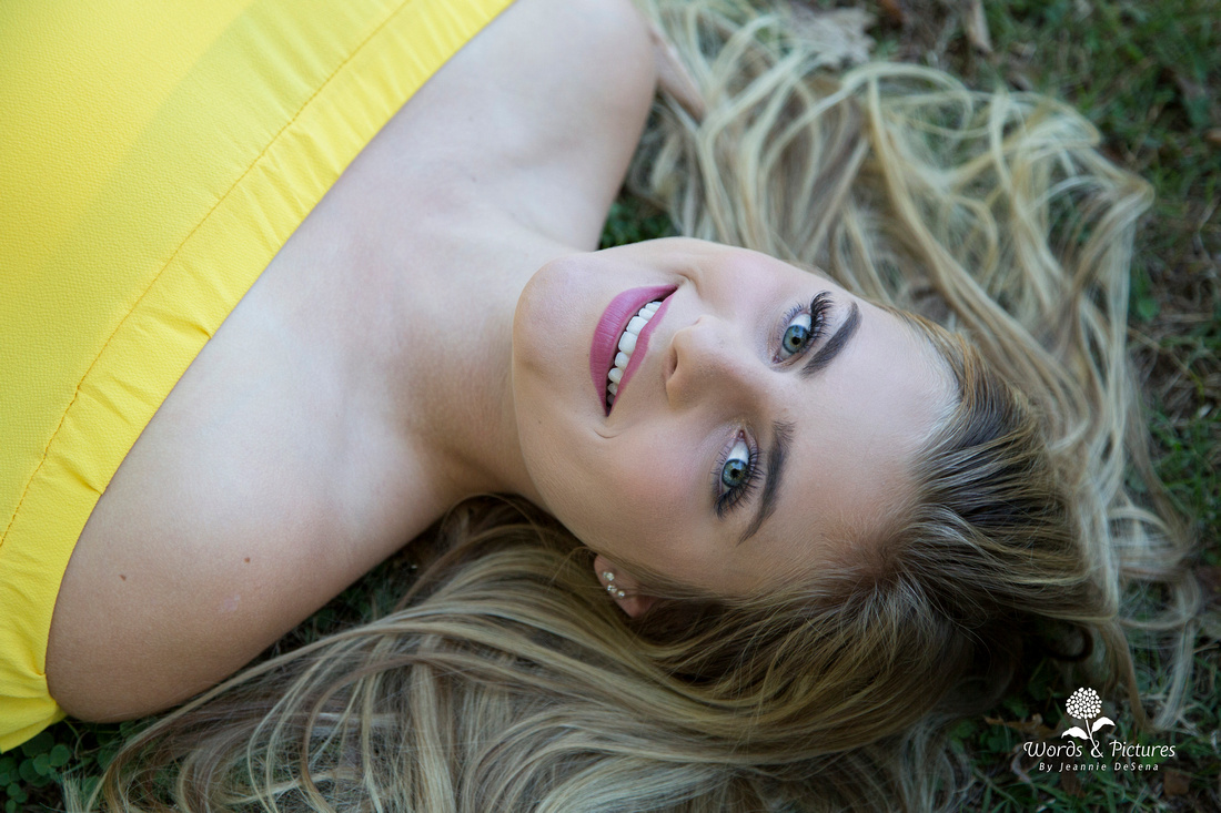 Kayla's hair fans around her face and shoulders as she looks up at the camera while lying on the ground. Her yellow, off-the-shoulder top provides a pop of color.