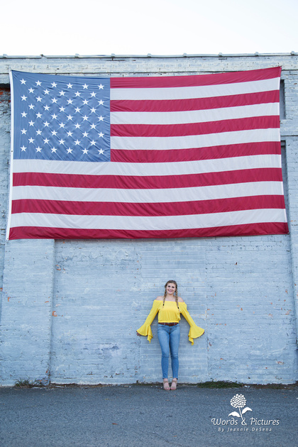 Davidson, North Carolina, served as the small-town USA setting for the first part of Kayla's session. She stands with her back to a brick wall, hands outstretched, with the flag above her.